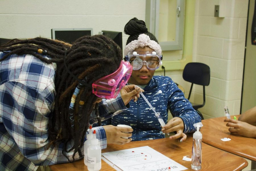 A member of UM-Flint's Chemistry Club interacts with an elementary school student.