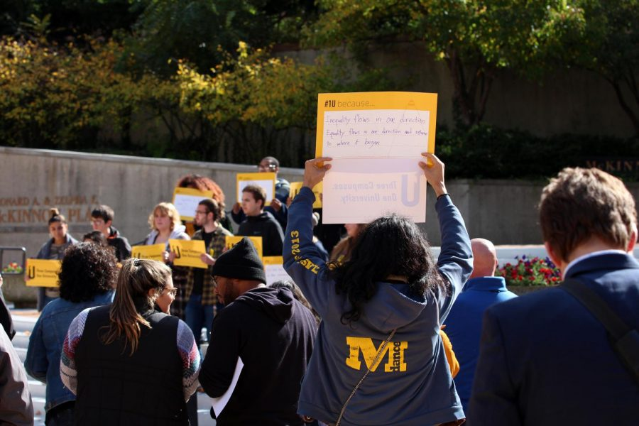 A student stands in protest of the university's mistreatment of UM-Flint students at a 1U Rally in McKinnon Plaza