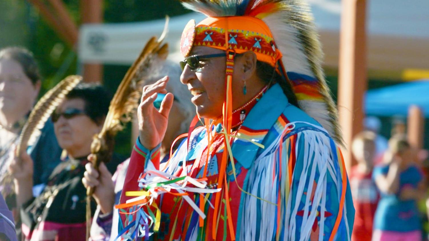 A male fancy dancer waits to perform at a summer pow wow.