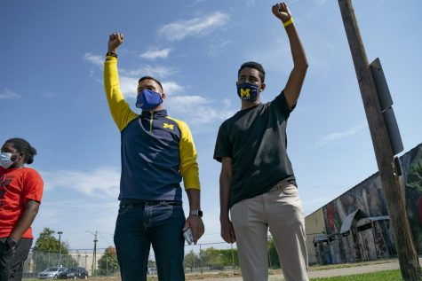 Levi Todd (left) and Omar Elnour (right) hold their firsts up during a moment of silence for George Floyd at a Black Lives Matter rally held two weeks before the day of action.